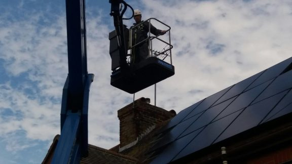 Removing pigeons from under the solar panels using a powered platform.