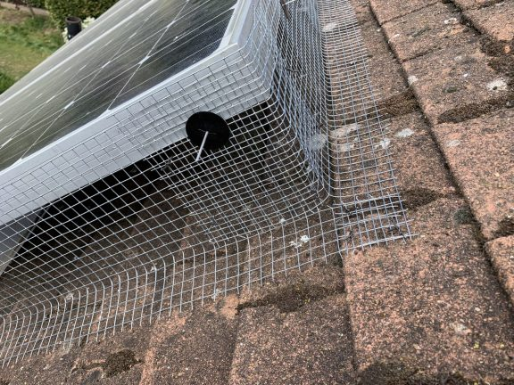 Mesh fitted round a corner with the use of a solar panel clip.